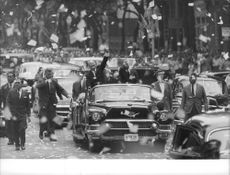 Dwight D. Eisenhower in a caravan, with a prominent man, waving, people are throwing papers as they welcome the president.