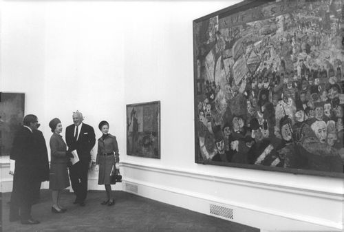 Queen Fabiola of Belgium standing with people and looking at an artwork.
