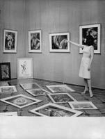 Ludmilla Tcherina pointing towards a painting hanging on wall.