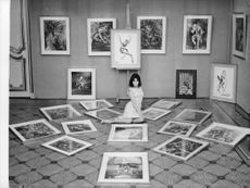 Ludmilla Tcherina sitting in the middle of scattered paintings.