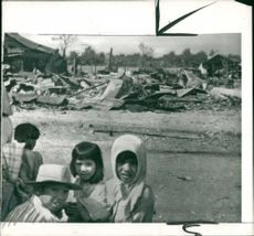 Vietnamese children in front of their wrecked homes after attack by Viet Cong