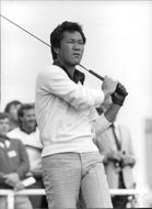 Isao Aoki standing and playing golf.