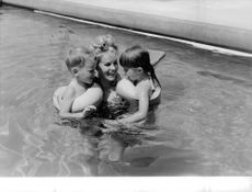 Carroll Baker bathing in swimming pool with children.