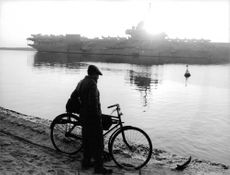 A man with his bike, standing by the shore, in the background is a Naval ship of Israel.