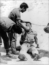 A soldier giving drink to his comrade. Israel.