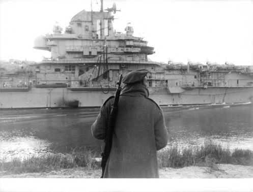 A man standing with a rifle in front of a military vessel in Israel.  - 1967