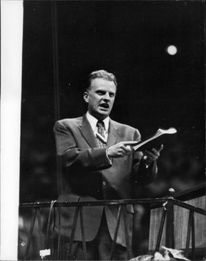 Billy Graham pointing towards the book and addressing.