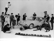 Photographers clicking picture of Volkswagen car.