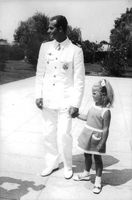 Prince Juan Carlos holding his young daughter's hand.