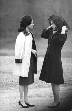 Princess Irene standing and  listening to a woman while putting a cloth on her head, April 1964.
