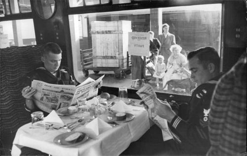 US Navy officers reading newspaper.