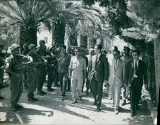 Ahmed Ben Bella walking with his officials.