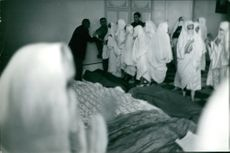 Women wearing White Burka gathered in a place.
