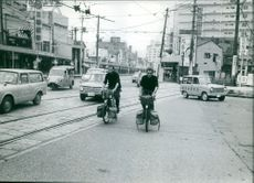 Two men riding a bicycle in the street. Photo taken Oct 1964