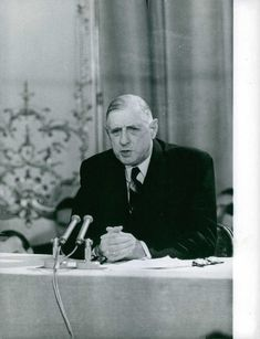 Charles de Gaulle speaking in the microphone during a press conference.