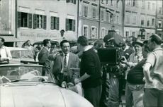 Mario Del Monaco talking to man, surrounded by people.