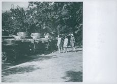 Children looking at German army tanks in playground in park in Oslo , Norway 1943.