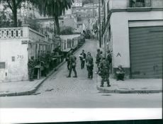 Man carrying a baby passing by soldiers in a street in Algeria.