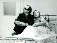 Morecambe and Wise sitting on bed and looking up.