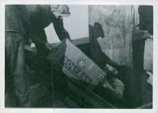 Men lifting box, transporting eggs to Germany from Norway. 1941.