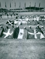 Children on the field holding flag of different countries, in Tokyo, Japan.