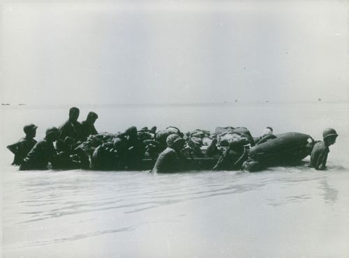 Soldiers pushing a lifeboat in the sea with bodies in it, in Vietnam.