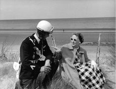Mamie Eisenhower sitting outside with man in uniform and helmet.
