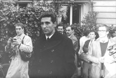 Gilbert Bécaud walking in the street while taking him a picture.