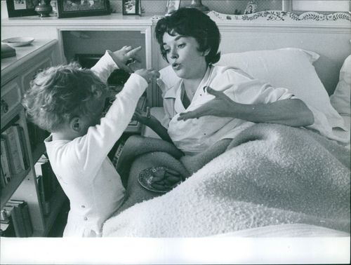 Dawn Addams playing with her child.