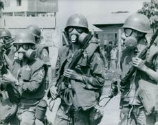 Soldiers pictured wearing gas masks on the streets of Vietnam. 1965.