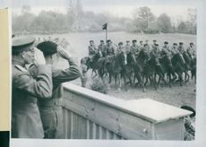 Field Marshal Montgomery takes the salute as a regiment of Cossacks rides past. With him is Marshal Rokossovsky and Russian and British officers.