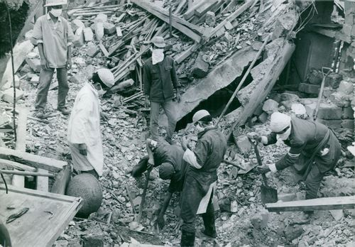 Several men standing on a rubble of a collapsed building.