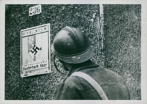 A soldier looking at a Nassi sign hanging on the wall during the Tyskland war, 1939.