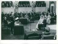Princess Margriet Francisca of the Netherlands and Pieter van Vollenhoven, Jr., sits on a chair as they listen to the man talking in front on their wedding day.