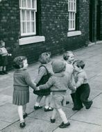 Young boys and girls happily playing on the sidewalk.