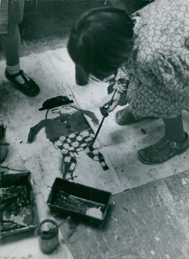 A girl bending over to paint Humpty Dumpty on a canvass lying on the floor.