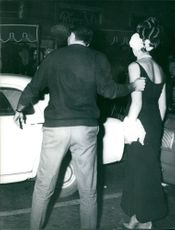 A man leads April Ashley get in to a car. 1964.