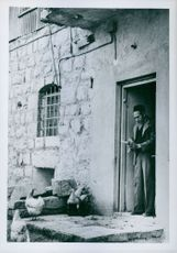 An old man standing in doorway.