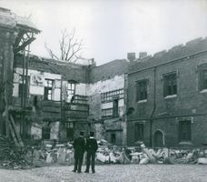 2 Men looking at a building damaged by the bombings. 1946.