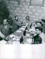 Men having their meal, with wine and lighted candles, in Vietnam.