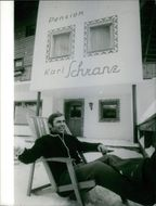 Karl Schranz sitting outside a building named after him.