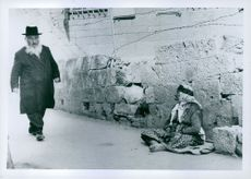Man walking and woman sitting, Israel at the time of trial of Eichmann, 1961.
