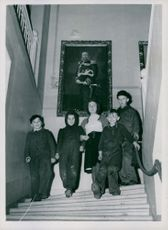 Photo of children climbing down the stairs with the portrait of Theold Onner on the background.