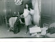 Dalida smiles for the camera while she was being helped by a woman for a fitting.