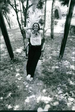 Claudine Auger riding a swing, smiling.
