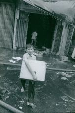 A wet boy crossing on a flooded street of Saigon carrying a box during the war in Vietnam, 1968.