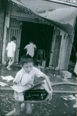 A vintage photo of children evacuating all their necessary materials in their homes during war in Vietnam.