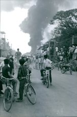 People in the street of Saigon looking at the burning building during the war in Vietnam, 1968.