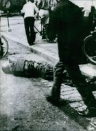 A vintage photo of a soldier lying dead in a road of Saigon during Vietnam war.