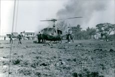 A vintage photo of a helicopter rescuing wounded soldiers during war in Vietnam.